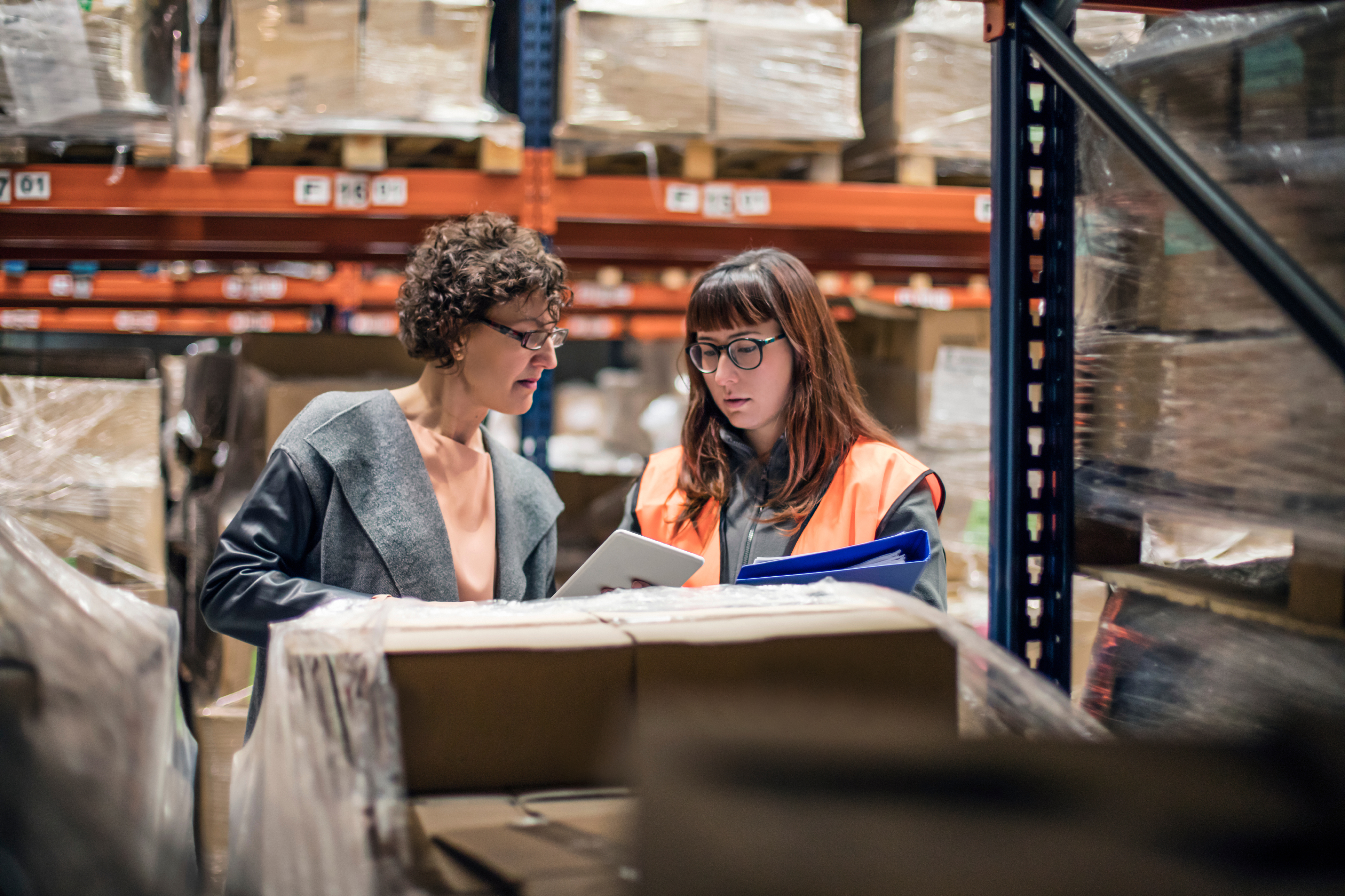 Woman with digital tablet in warehouse talking to worker in the aisle.